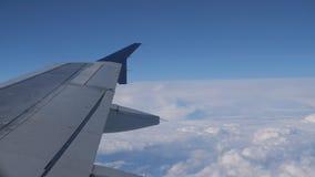 Πετώντας στο αεροπλάνο πέρα από την επιφάνεια σύννεφων, άποψη από το παράθυρο στο φτερό φιλμ μικρού μήκους
