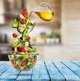 Πετώντας φυτική ελληνική σαλάτα με την έκχυση του ελαιολάδου από το πιατάκι Στοκ εικόνα με δικαίωμα ελεύθερης χρήσης