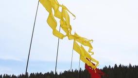 Πετώντας φωτεινά κίτρινα και κόκκινα εμβλήματα στα κοντάρια σημαίας στο υπόβαθρο ουρανού κατά τη διάρκεια του θερινού φεστιβάλ φιλμ μικρού μήκους