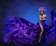 Πετώντας ύφασμα φορεμάτων λουλουδιών γυναικών, πρότυπο μόδας στο ιώδες καπέλο Στοκ Εικόνες