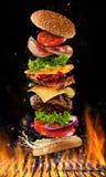 Πετώντας burger συστατικά επάνω από τη σχάρα Στοκ εικόνα με δικαίωμα ελεύθερης χρήσης
