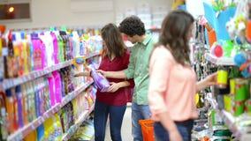 Πελάτες που επιλέγουν τα καθαρίζοντας προϊόντα στην υπεραγορά απόθεμα βίντεο