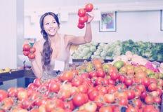 Πελάτης γυναικών που κρατά τις ώριμες ντομάτες στην υπεραγορά Στοκ φωτογραφίες με δικαίωμα ελεύθερης χρήσης
