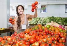 Πελάτης γυναικών που κρατά τις ώριμες ντομάτες στην υπεραγορά Στοκ Εικόνες