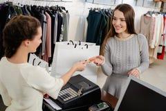 Πελάτης γυναικών που πληρώνει με την πιστωτική κάρτα στην αίθουσα εκθέσεως Στοκ φωτογραφία με δικαίωμα ελεύθερης χρήσης