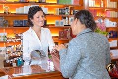 Πελάτης και πωλητής που κουβεντιάζουν στην αρωματοποιία Στοκ φωτογραφία με δικαίωμα ελεύθερης χρήσης