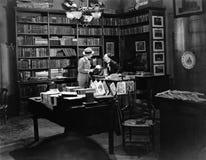 Πελάτης και υπάλληλος στο κατάστημα βιβλίων (όλα τα πρόσωπα που απεικονίζονται δεν ζουν περισσότερο και κανένα κτήμα δεν υπάρχει  Στοκ φωτογραφίες με δικαίωμα ελεύθερης χρήσης