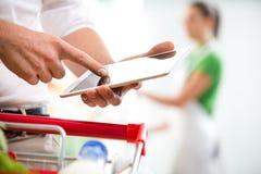 Πελάτης με την ταμπλέτα στην υπεραγορά Στοκ Εικόνες