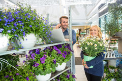 Πελάτης με το δοχείο λουλουδιών που υποστηρίζει τον ανθοκόμο που χρησιμοποιεί το κινητό τηλέφωνο στοκ εικόνα με δικαίωμα ελεύθερης χρήσης