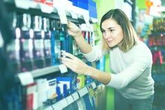 Πελάτης νέων κοριτσιών που ψάχνει αποτελεσματικό mouthwash στο supermark στοκ φωτογραφίες