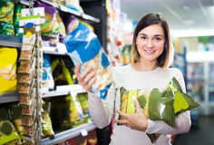 Πελάτης νέων κοριτσιών που ψάχνει τα νόστιμα πρόχειρα φαγητά στην υπεραγορά Στοκ εικόνα με δικαίωμα ελεύθερης χρήσης