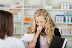 Πελάτης που βήχει μπροστά από το φαρμακοποιό στοκ φωτογραφίες με δικαίωμα ελεύθερης χρήσης