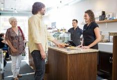 Πελάτης που διατάζει τα τρόφιμα στη σερβιτόρα στην καφετέρια Στοκ Φωτογραφίες