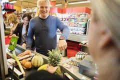 Πελάτης που παρουσιάζει Smartwatch στον ταμία στην υπεραγορά Στοκ Εικόνα