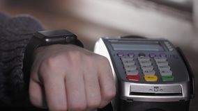 Πελάτης που πληρώνει με την τεχνολογία NFC από το έξυπνο ρολόι ανέπαφο στο τερματικό στο σύγχρονο καφέ απόθεμα βίντεο