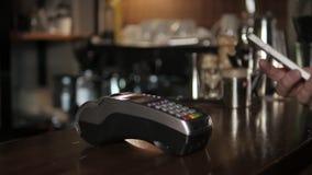 Πελάτης που πληρώνει με την τεχνολογία NFC με κινητό τηλέφωνο στο τερματικό στο σύγχρονο καφέ απόθεμα βίντεο