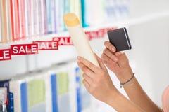Πελάτης που φωτογραφίζει το καλλυντικό προϊόν στην υπεραγορά Στοκ Εικόνες