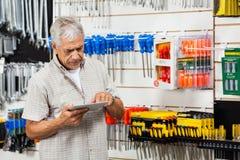 Πελάτης που χρησιμοποιεί τον υπολογιστή ταμπλετών στο κατάστημα υλικού Στοκ Εικόνα