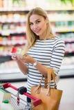 Πελάτης στην υπεραγορά που κρατά ένα προϊόν και ένα χαμόγελο Στοκ Εικόνα