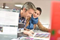Πελάτης στο κατάστημα εκτύπωσης που ελέγχει την ποιότητα τυπωμένων υλών στοκ εικόνα με δικαίωμα ελεύθερης χρήσης