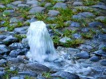 Πηγή καθαρού νερού σε έναν στρωμένο πέτρα δρόμο Στοκ Εικόνες