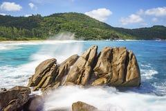 Πηγή νερού πέρα από τους βράχους γρανίτη, άγρια τροπική παραλία με τους φοίνικες Στοκ φωτογραφίες με δικαίωμα ελεύθερης χρήσης