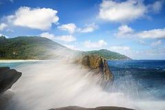 Πηγή νερού πέρα από τους βράχους γρανίτη, άγρια τροπική παραλία με τους φοίνικες Στοκ Φωτογραφίες