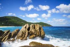 Πηγή νερού πέρα από τους βράχους γρανίτη, άγρια τροπική παραλία με τους φοίνικες Στοκ Εικόνα