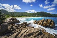 Πηγή νερού πέρα από τους βράχους γρανίτη, άγρια τροπική παραλία με τους φοίνικες Στοκ Εικόνες