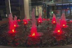 Πηγή που φωτίζεται στο κόκκινο κοντά στο κτίριο γραφείων Στοκ Φωτογραφία
