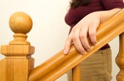 Πηγαίνετε κάτω από τα σκαλοπάτια με το χέρι στο κιγκλίδωμα Στοκ Εικόνες