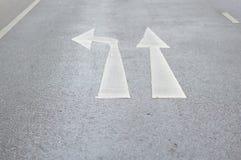 Πηγαίνετε κατ' ευθείαν ή γυρίστε το αριστερό σημάδι κυκλοφορίας στο στρωμένο δρόμο στοκ φωτογραφία με δικαίωμα ελεύθερης χρήσης