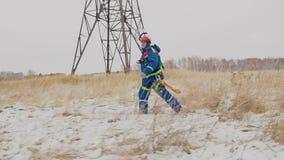 Πηγαίνοντας επισκευή ηλεκτρολόγων τα καλώδια στο ηλεκτροφόρο καλώδιο στον τομέα στο χιόνι απόθεμα βίντεο