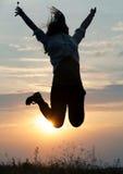 Πηδώντας γυναίκα και ηλιοβασίλεμα silhouett Στοκ φωτογραφία με δικαίωμα ελεύθερης χρήσης