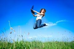 Πηδώντας γυναίκα με το lap-top Στοκ Φωτογραφίες