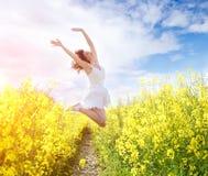Πηδώντας γυναίκα στον κίτρινο τομέα Στοκ εικόνα με δικαίωμα ελεύθερης χρήσης