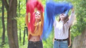 Πηδώντας νέες γυναίκες με το μπλε και κόκκινο ύφασμα στο θερινό πάρκο απόθεμα βίντεο