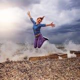 Πηδώντας γυναίκα στην παραλία Στοκ Εικόνες