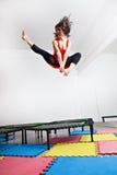 Πηδώντας νέα γυναίκα σε ένα τραμπολίνο Στοκ Φωτογραφία