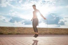 Πηδώντας σχοινιών ατόμων άλματος φλόγα φακών φλογών φακών ήλιων ηλιόλουστη υπαίθρια Στοκ Φωτογραφίες