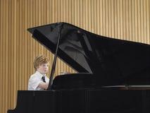 Πιάνο παιχνιδιού αγοριών στην κατηγορία μουσικής Στοκ φωτογραφία με δικαίωμα ελεύθερης χρήσης