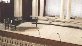 Πιάνο στη σκηνή και κενές καρέκλες στη αίθουσα συναυλιών στοκ εικόνες