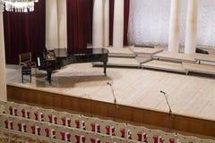 Πιάνο στη σκηνή και κενές καρέκλες στη αίθουσα συναυλιών στοκ εικόνα με δικαίωμα ελεύθερης χρήσης