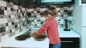 Πιάτα πλύσης μικρών κοριτσιών στην κουζίνα απόθεμα βίντεο