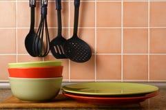 Σωρός των πιάτων σε ένα υπόβαθρο ενός κεραμικού κεραμιδιού Στοκ Φωτογραφίες