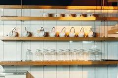 Πιάτα στα ράφια στο εστιατόριο σε ένα ελαφρύ υπόβαθρο στοκ φωτογραφία με δικαίωμα ελεύθερης χρήσης