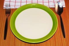 Πιάτο, δίκρανο και κουτάλι στο ξύλινο υπόβαθρο Στοκ εικόνα με δικαίωμα ελεύθερης χρήσης