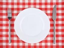Πιάτο, δίκρανο, μαχαίρι σε ένα κόκκινο ελεγμένο τραπεζομάντιλο Στοκ Εικόνες