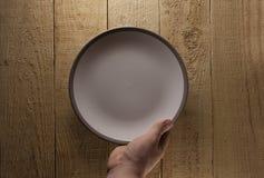 Πιάτο λαβής χεριών στο ξύλο Στοκ εικόνα με δικαίωμα ελεύθερης χρήσης