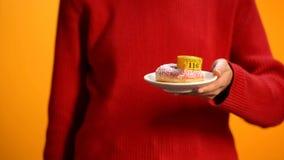 Πιάτο γυναικείας εκμετάλλευσης με doughnut και τη μέτρηση της ταινίας, ανθυγειινή διατροφή, κίνδυνος παχυσαρκίας στοκ φωτογραφίες